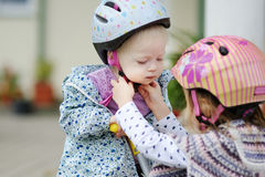 Little girl hepling her sister to put a helmet Royalty Free Stock Photography