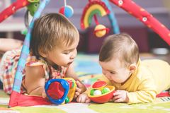 Little Girl And Her Baby brother Playing With Toys Together. Little Girl And Her Baby brother Are Playing With Toys Together At Home royalty free stock photos