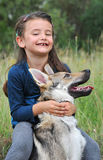 Little girl and her baby wolf dog stock photo