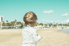 Little girl with her back to the beach. Little girl on her back on the beach. Blonde girl on the beach Stock Photo