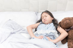 A little girl in her bed has a stomachache Stock Photo