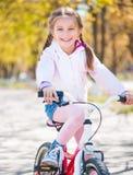Little girl on her bike Stock Images