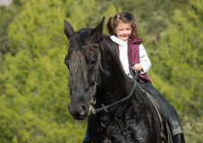 Little girl and her black horse Stock Images