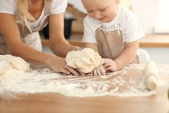 Little girl and her blonde mom in beige aprons playing and laughing while kneading the dough in kitchen. Homemade pastry royalty free stock photos
