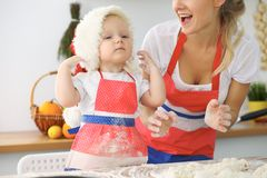 Little girl and her blonde mom in red aprons  playing and laughing while kneading the dough in the kitchen. Homemad Royalty Free Stock Photo