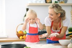 Little girl and her blonde mom in red aprons  playing and laughing while kneading the dough in the kitchen. Homemad Royalty Free Stock Photos