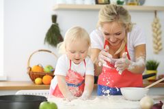 Little girl and her blonde mom in red aprons  playing and laughing while kneading the dough in the kitchen. Homemad Stock Photography