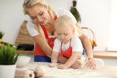 Little girl and her blonde mom in red aprons playing and laughing while kneading the dough in kitchen. Homemade pastry royalty free stock images