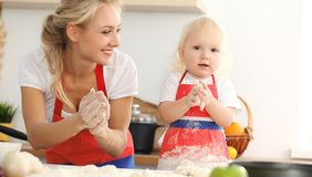 Little girl and her blonde mom in red aprons playing and laughing while kneading the dough in kitchen. Homemade pastry stock photo