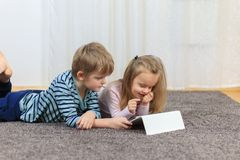 Little girl with her brother using tablet computer at home stock photo