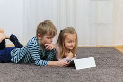 Little girl with her brother using tablet computer at home royalty free stock image