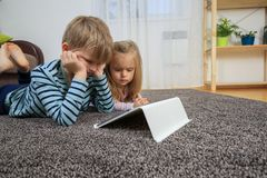 Little girl with her brother using tablet computer at home royalty free stock photos