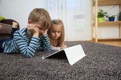 Little girl with her brother using tablet computer at home royalty free stock images