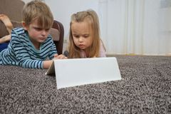 Little girl with her brother using tablet computer at home royalty free stock photo