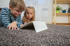 Little girl with her brother using tablet computer at home royalty free stock photography