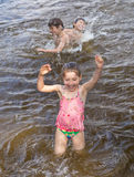 Little girl and her brothers are playing in a lake Royalty Free Stock Images