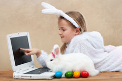 Little girl with her bunny using computer together Royalty Free Stock Photography