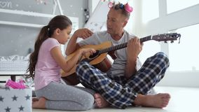 Little girl and her caring father playing the guitar stock video footage