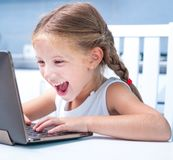Little girl with her computer Stock Image