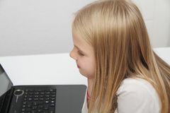 Little girl with her computer at home at the table Royalty Free Stock Photos