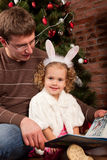 Little girl with her dad near Christmas tree Royalty Free Stock Images