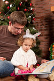 Little girl with her dad near Christmas tree Stock Photo
