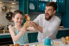 Little girl and her dad. Playing in the kitchen. Amusing cooking activity and tons of positive emotions stock image