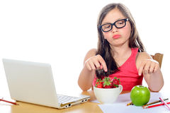 A little girl at her desk looking at his snack Royalty Free Stock Photos