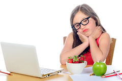 A little girl at her desk looking at his snack Stock Photography