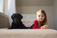 Little girl and her dog on the bed. Royalty Free Stock Photo