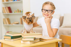 Little girl and her dog wearing glasses. Royalty Free Stock Image