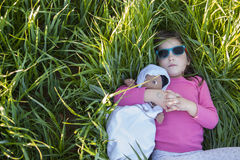 Little girl and her doll lying on green cereal field at sunset Royalty Free Stock Photo