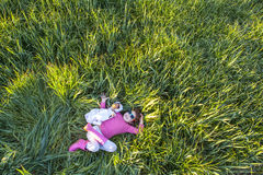 Little girl and her doll lying on green cereal field at sunset Stock Photography