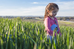 Little girl and her doll walking through green cereal field at s Stock Images