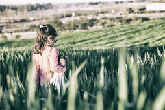 Little girl and her doll walking through green cereal field at s Royalty Free Stock Photos