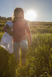 Little girl and her doll walking through green cereal field at s Stock Photos