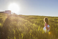 Little girl and her doll walking to the sun through green cereal Stock Images