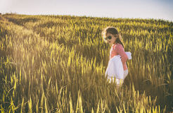 Little girl and her doll walking uphill by green cereal field Stock Image