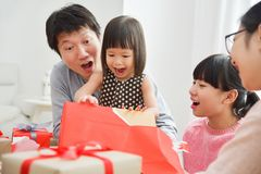 Little girl with her family unwrapping a red gift box. Stock Photos