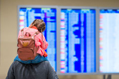 Little girl with her father background flight information at airport Stock Images