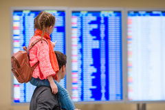 Little girl with her father background flight information at airport Royalty Free Stock Photos