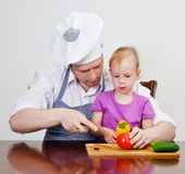Little girl and her father cutting vegetables Stock Photo