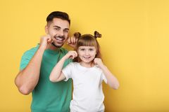 Little girl and her father flossing teeth on color background. Space for text royalty free stock image