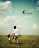 Little girl and her father with flying a kite Royalty Free Stock Photos