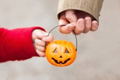 Little girl and her father, Halloween, parent and child trick or treating together. Toddler kid with jack-o-lantern. Kid with candy bucket, closeup. Cold stock photography