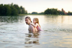 Little girl and her father having fun in a river Royalty Free Stock Images