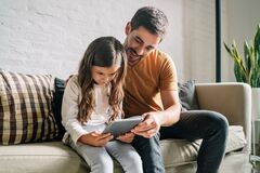 Little girl and her father using a digital tablet at home.