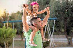 Little Girl And Her Father At Playground. Little girl is having fun with her father at playground royalty free stock photo
