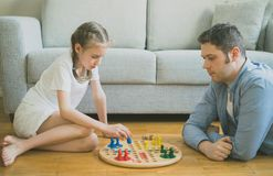 Family playing ludo. Little girl and her father playing ludo Stock Images