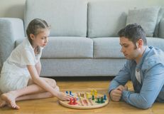 Family playing ludo. Little girl and her father playing ludo Royalty Free Stock Photos